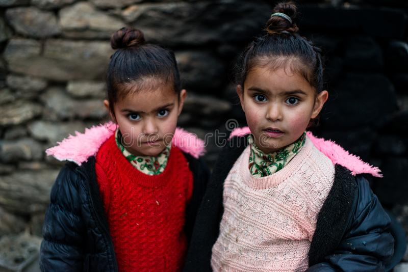 Kullu, Himachal Pradesh, India - December 21, 2018 : Photo of poor indian Twins girl child in mountains. Smile beautiful face female happy person portrait young royalty free stock photo
