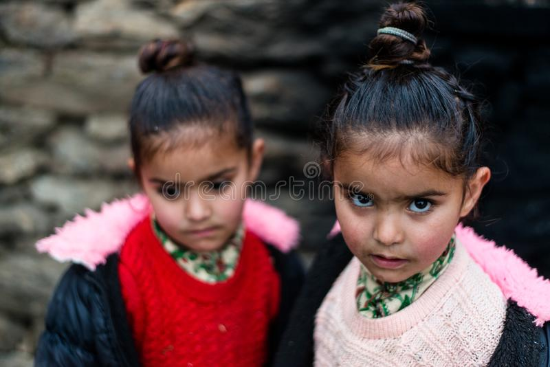 Kullu, Himachal Pradesh, India - December 21, 2018 : Photo of poor indian Twins girl child in mountains. Smile beautiful face female happy person portrait young stock photo