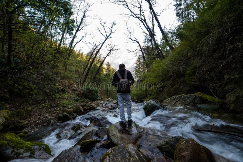 Kullu, Himachal Pradesh, India - March 01, 2019 - Traveller at milky water stream in himalayas - waterfall. In india royalty free stock image