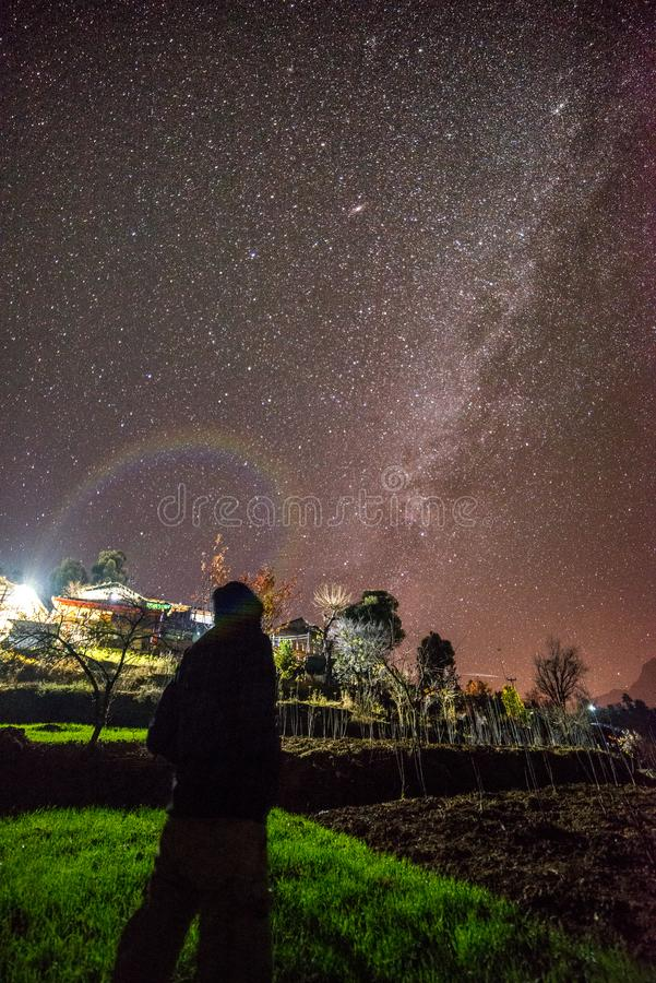 Kullu, Himachal Pradesh, India - November 30, 2018 : Boy under milkyway over indian village in Autumn season in mountains stock photography
