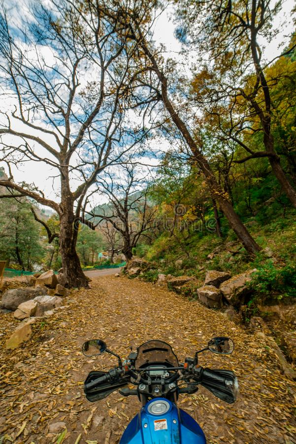 Kullu, Himachal Pradesh, India - November 26, 2018 : Ride in Autumn - Beautiful landscape with rural road, trees with red and. Orange leaves in himalays stock photography