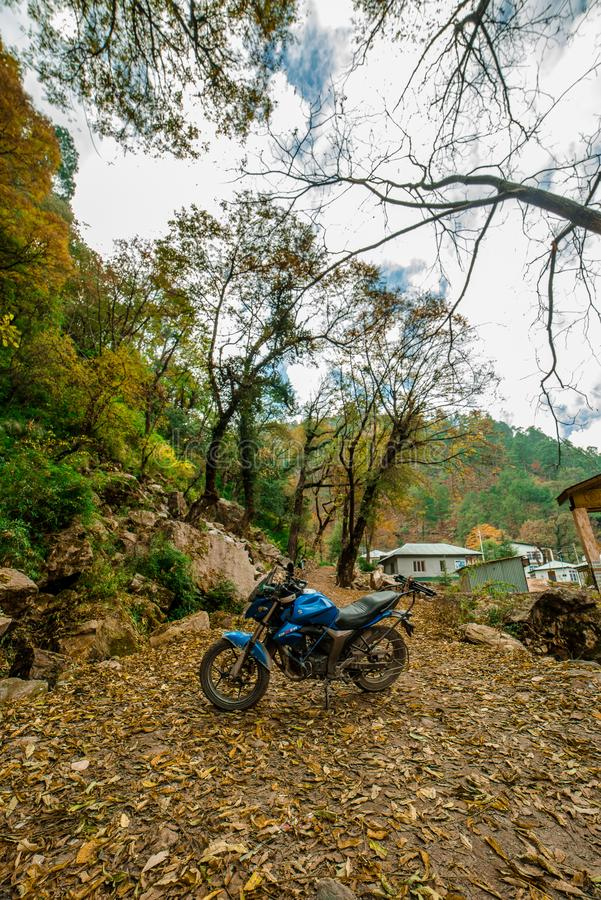 Kullu, Himachal Pradesh, India - November 26, 2018 : Ride in Autumn - Beautiful landscape with rural road, trees with red and. Orange leaves in himalays royalty free stock photography