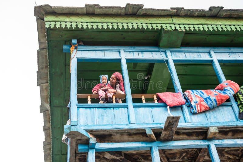 Kullu, Himachal Pradesh, la India - 26 de noviembre de 2018: Foto del bebé himalayan con la madre en la casa de madera, gente Him imagen de archivo