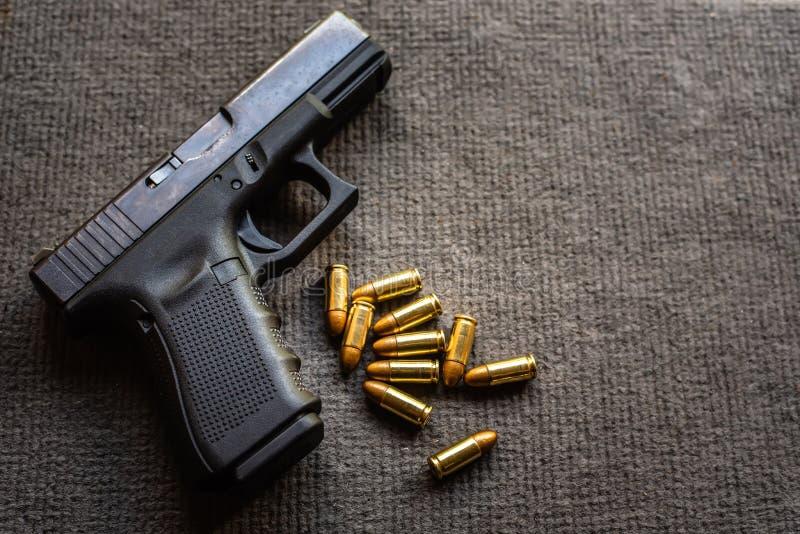 Kulor och 9mm vapen på det svarta sammetskrivbordet royaltyfri foto