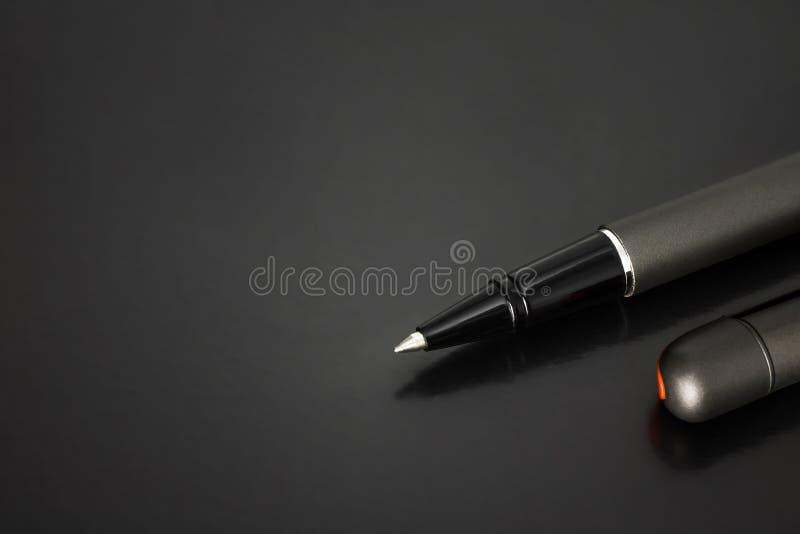 Kulspetspenna- och pennlock på mörk bakgrund med lyxig stil royaltyfria foton