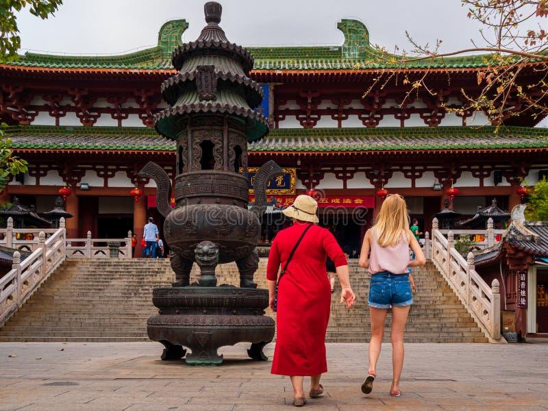 KULTURELLA NANSHAN PARKERAR, HAINAN, KINA - turister f?r 5 MARS 2019 - tv? caucasian kvinnliga p? en kinesisk tempel royaltyfri foto