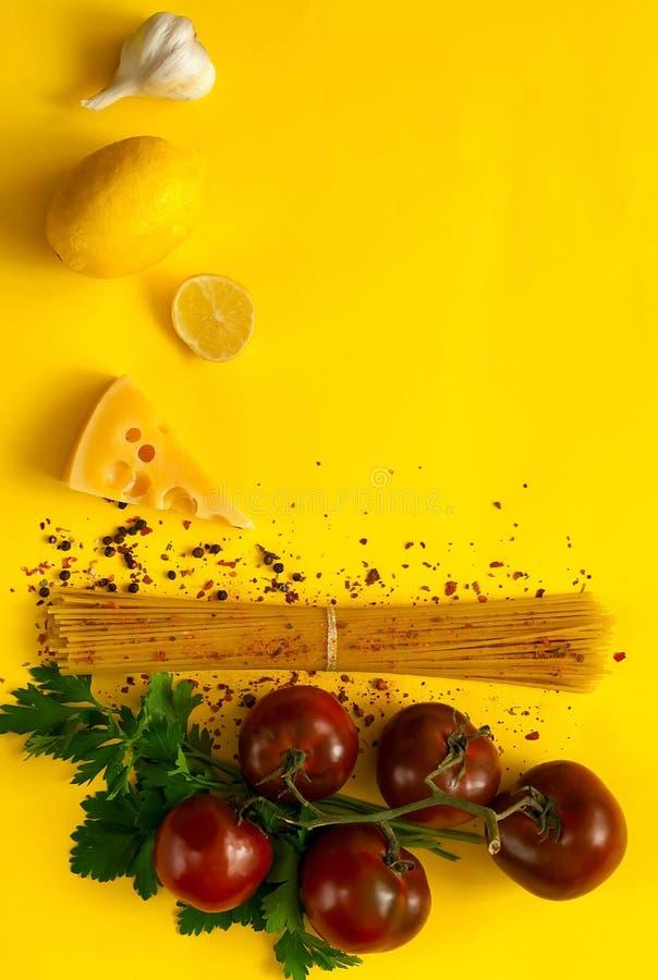 Kumato et ingrédients de tomates pour faire cuire des pâtes sur le fond jaune Vue faite de produits biologiques Concept de nourri image stock