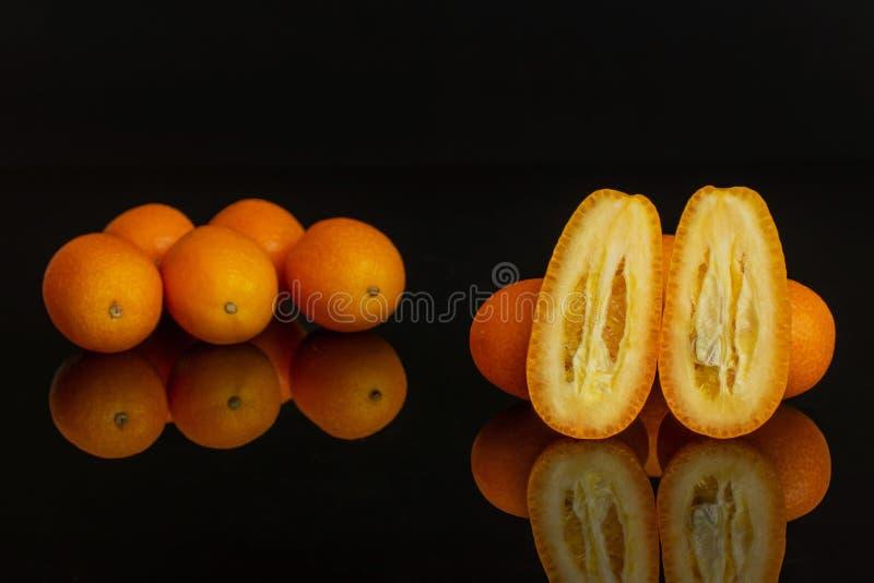 Kumquat alaranjado fresco isolado no vidro preto fotos de stock