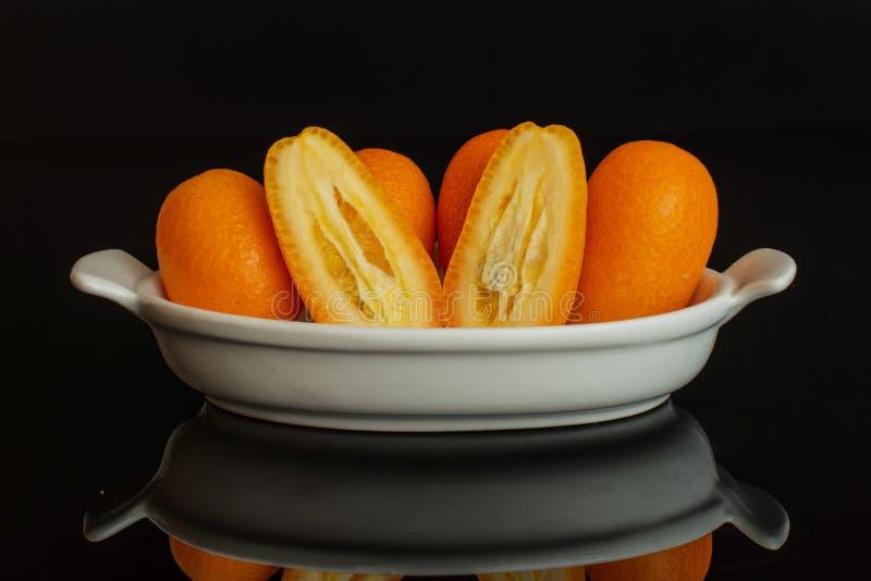 Kumquat alaranjado fresco isolado no vidro preto fotos de stock royalty free