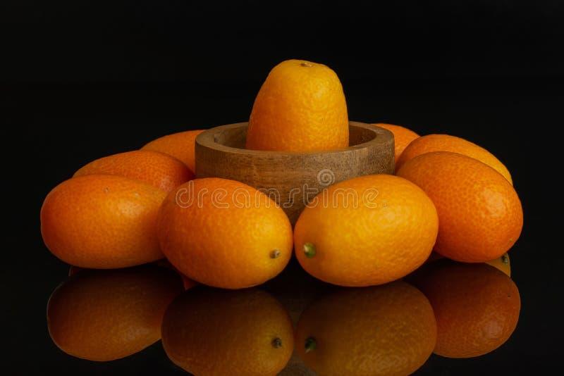 Kumquat alaranjado fresco isolado no vidro preto foto de stock