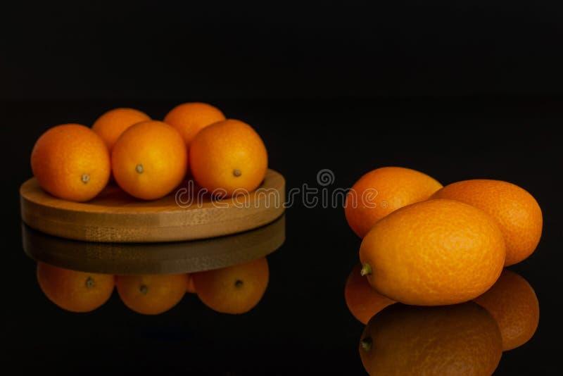 Kumquat alaranjado fresco isolado no vidro preto imagem de stock royalty free