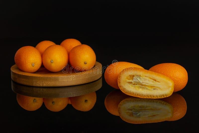 Kumquat alaranjado fresco isolado no vidro preto imagens de stock