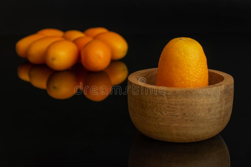 Kumquat alaranjado fresco isolado no vidro preto imagens de stock royalty free