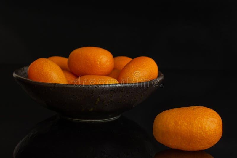 Kumquat alaranjado fresco isolado no vidro preto foto de stock royalty free