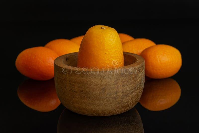 Kumquat alaranjado fresco isolado no vidro preto fotografia de stock