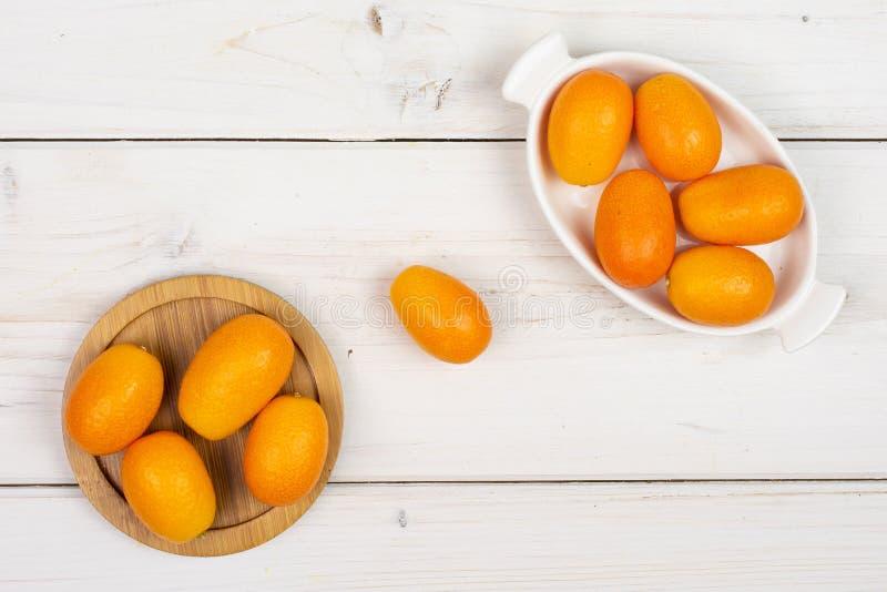 Kumquat alaranjado fresco na madeira cinzenta imagem de stock