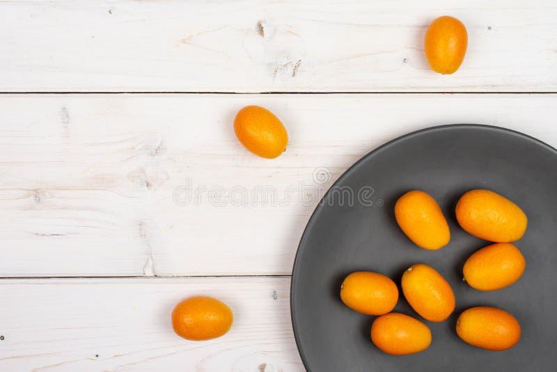 Kumquat alaranjado fresco na madeira cinzenta foto de stock