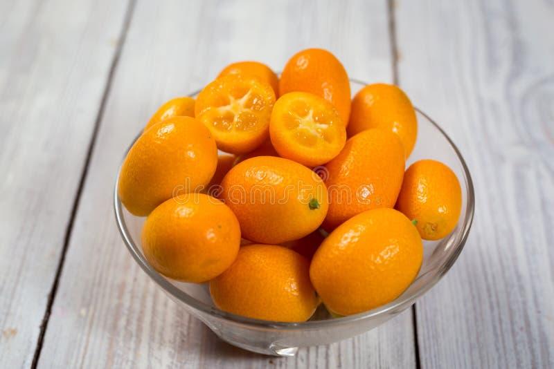 Kumquat em uma placa, Kumquats alaranjados orgânicos crus, laranjas pequenas CH imagem de stock royalty free