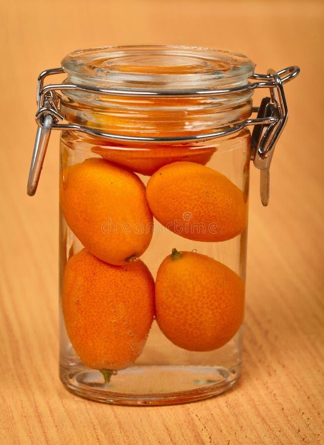 Kumquat na lata de estanho pequena no fundo de madeira imagem de stock