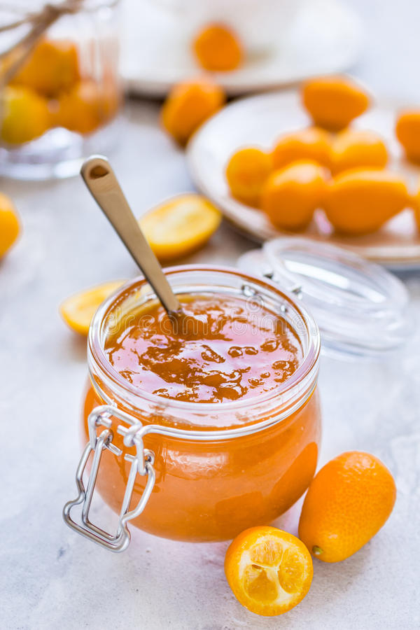 Kumquat na placa e no doce no frasco no fundo cinzento imagem de stock