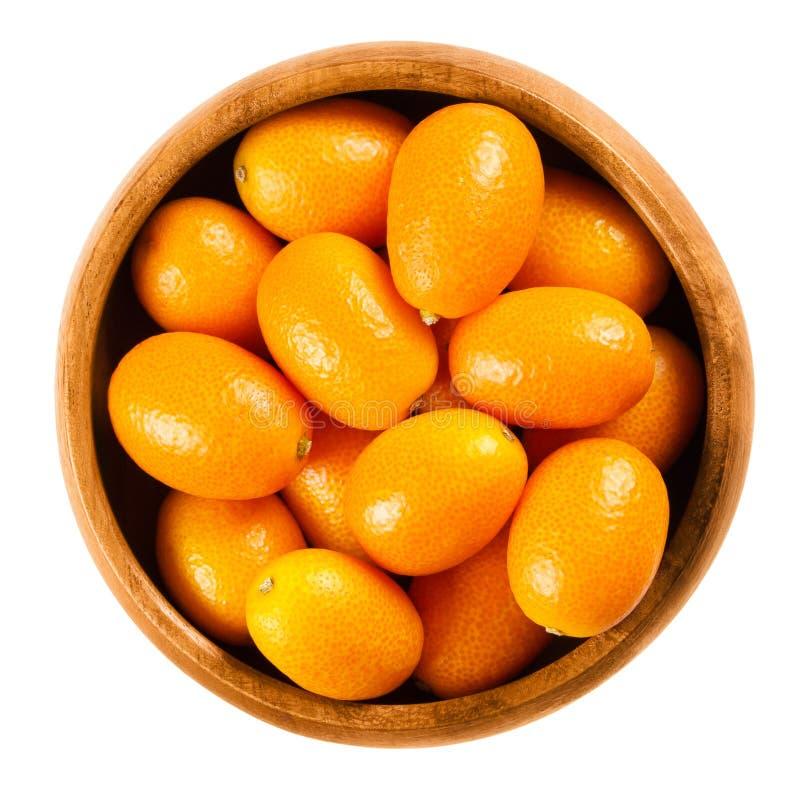 Kumquats frescos em uma bacia de madeira no fundo branco imagens de stock royalty free