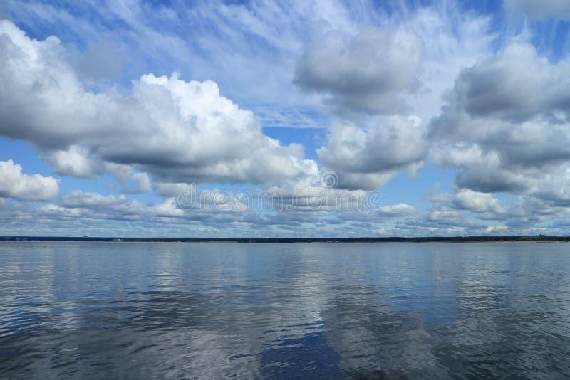 Kumuluswolken reflektierten sich im Seepanorama stockfotografie