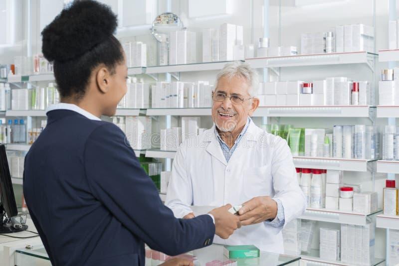 Kund för kemistGiving Medicine To kvinnlig arkivfoton
