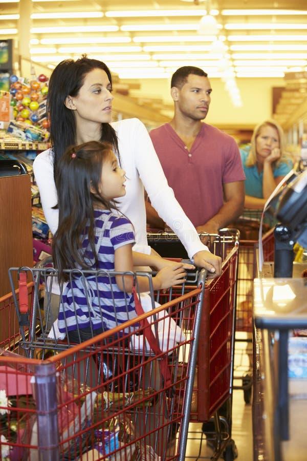 Kund i köen som betalar för att shoppa på supermarketkontrollen arkivfoton
