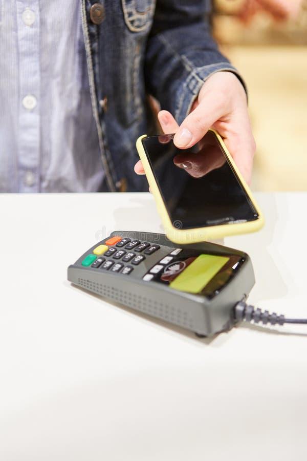 Kund med smartphonen på kortterminalen arkivfoton