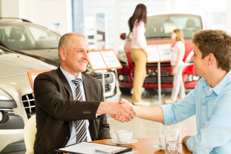 Kund och bilförsäljare som skakar händer royaltyfri fotografi