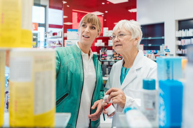 Kund och försäljningskvinna i apotek arkivfoto