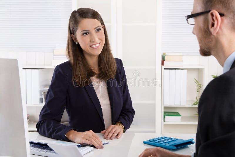 Kund och kvinnligt finansiellt medel i en diskussion på skrivbordet arkivbilder