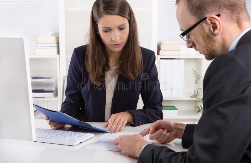 Kund och kvinnligt finansiellt medel i en diskussion på skrivbordet royaltyfri fotografi