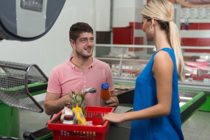Kund som använder kreditkorten på supermarketkontrollen royaltyfri foto
