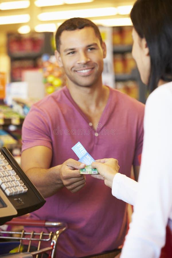 Kund som använder kuponger på supermarketkontrollen royaltyfri fotografi
