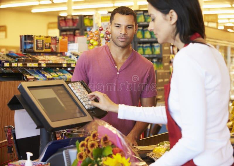 Kund som betalar för att shoppa på supermarketkontrollen arkivfoto