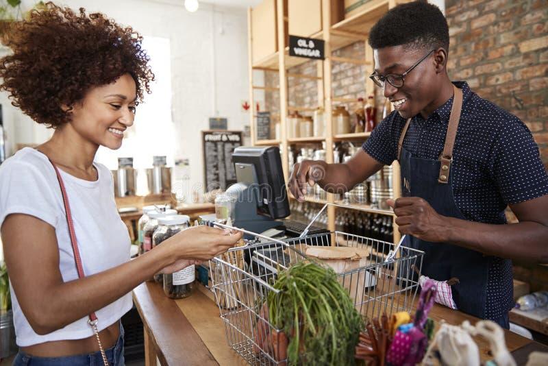 Kund som betalar för shopping på kontrollen av den hållbara plast- fria livsmedelsbutiken arkivbilder