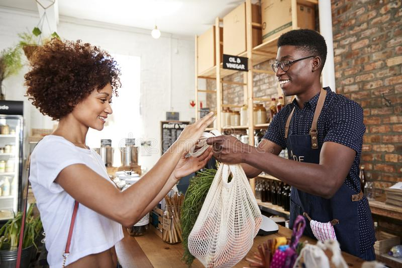 Kund som betalar för shopping på kontrollen av den hållbara plast- fria livsmedelsbutiken royaltyfri bild