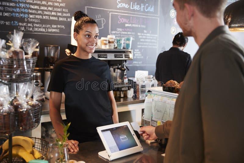 Kund som betalar i coffee shop genom att använda kreditkorten arkivbilder