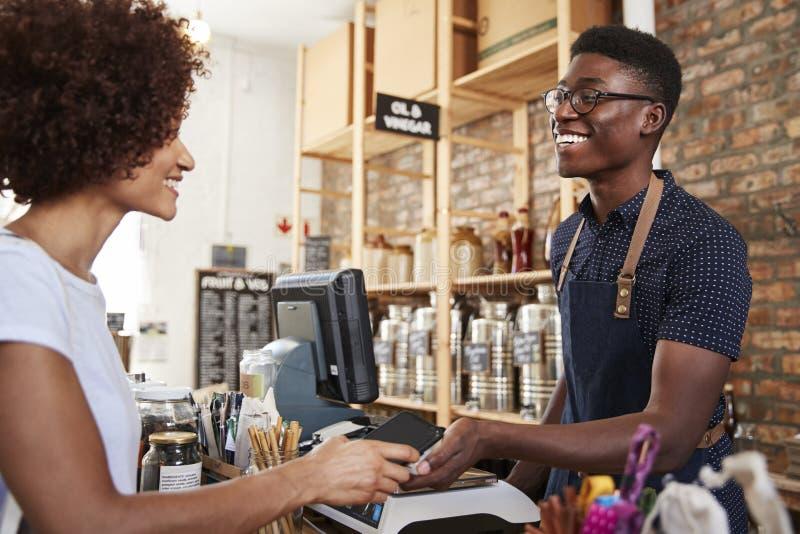 Kund som gör Contactless betalning för shopping på kontrollen av livsmedelsbutiken genom att använda mobiltelefonen arkivbild