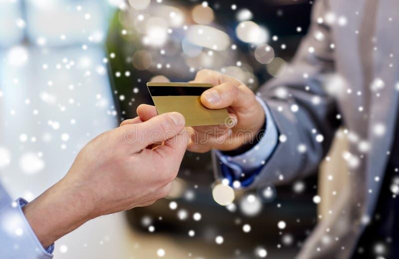 Kund som ger kreditkorten till bilåterförsäljaren i salong royaltyfria foton