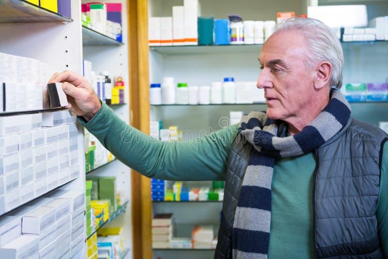 Kund som kontrollerar en preventivpillerask arkivfoton