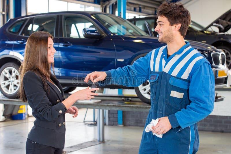 Kund som mottar tangenterna av hennes nya bil från en mechan service arkivbild