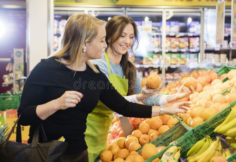 Kund som väljer apelsiner av försäljaren In Store royaltyfri bild