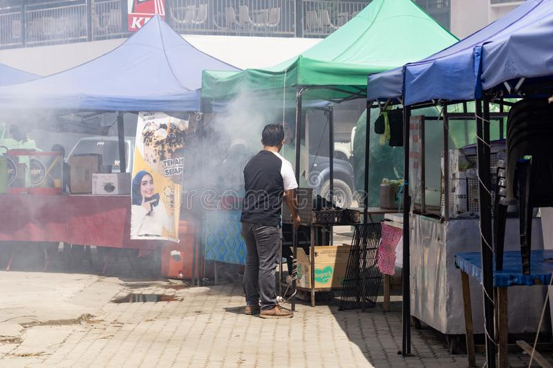 Smokey BBQ setting up for night market. KUNDASANG SABAH - MAY 27 2019;  Village markets operator prepaing food sales creating haze of barbeque smoke stock images