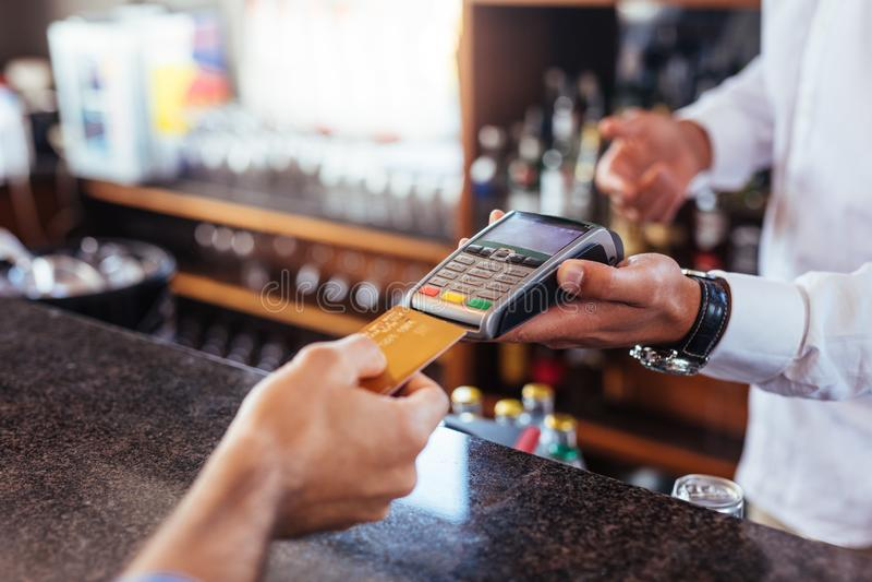Kunddanandebetalning genom att använda kreditkorten på stången royaltyfri foto