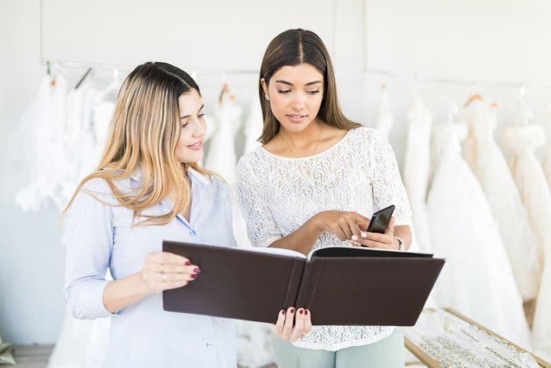 Kunde, der dem Geschäftsinhaber ihre Brautkleiderwahl zeigt stockbilder