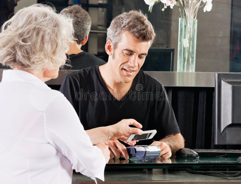 Kunde, der durch Handy am Salon zahlt stockbild