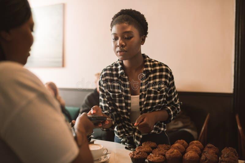 Kunde, der eine Kreditkarte verwendet, um für ihren Cappuccino zu zahlen lizenzfreie stockbilder