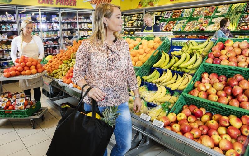 Kunde, der frische Früchte im Lebensmittelgeschäft betrachtet lizenzfreie stockfotos